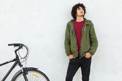 Male cyclist dressed in fashionable outfit, has curly hair, keeps hands in pocket of trousers, has little beard, looks thoghtfully royalty free stock photos