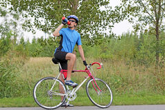 Male cyclist drink water. Male cyclist sitting on race bike and drink water Royalty Free Stock Photos