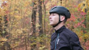 Male cyclist in fall park. Side view of portrait young professional cyclist puts on black helmet. Cycling concept.  stock video