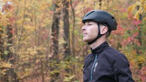 Male cyclist in fall park. Side view of portrait young professional cyclist puts on black helmet. Cycling concept. Slow motion.  stock video footage