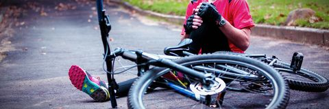 Male cyclist getting injured while falling from mountain bike stock photo