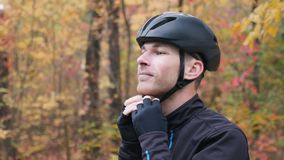 Male cyclist. Healthy young professional sportsman in activewear puts on black cycling helmet before training in fall park. Motiva. Ted athlete in autumn forest stock footage