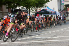 Male Cyclist Leads Pack Into Turn In Amateur Bike Race. Athens, GA, USA - April 25, 2015: A male cyclist leans into a turn as he leads a large group while racing royalty free stock photography