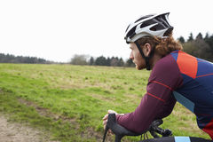 Male cyclist leaning on bike in open countryside, close up Stock Images