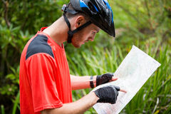 Male cyclist looking at map. In countryside Stock Photos