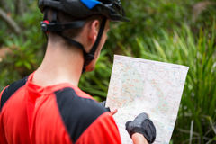 Male cyclist looking at map. In countryside Royalty Free Stock Photos