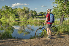 Male cyclist with a mountain bike on a lake shore. Summer scenery in Colorado Stock Image
