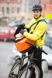 Male Cyclist Putting Package In Courier Bag On Royalty Free Stock Photos