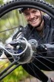 Male cyclist repairing his mountain bike. Portrait of smiling male cyclist repairing his mountain bike in park Stock Photos