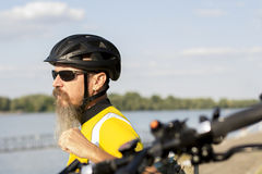 Male cyclist resting. And looking at river Royalty Free Stock Images