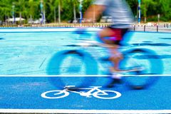 Male cyclist rides a bike on the lane of bicycle sign stock photography
