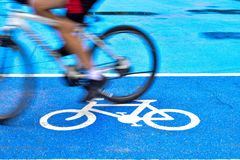 Male cyclist rides a bike on the lane of bicycle sign stock image