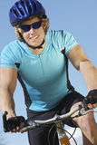 Male Cyclist Riding Bicycle. Happy young male cyclist riding bicycle against blue sky Stock Photography