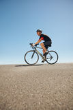 Male cyclist riding bicycle on flat road Stock Photo