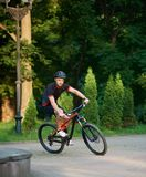 Male cyclist riding bike down park paved alley. Sporty male cyclist in sportswear training on bike, riding paved park alley. Muscle sportsman getting ready for Royalty Free Stock Photos