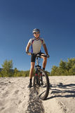 Male cyclist riding a bike stopped rolling on the sand Stock Photos