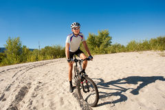 Male cyclist riding a bike stopped rolling on the sand Stock Photo
