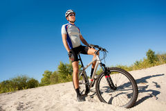 Male cyclist riding a bike stopped rolling on the sand. A male cyclist riding a bike stopped rolling on the sand; clear summer day Royalty Free Stock Photos