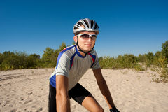 Male cyclist riding a bike stopped rolling on the sand Stock Image
