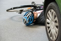 Male cyclist after road accident. Unconscious Male Cyclist Lying On Street After Road Accident Stock Photo
