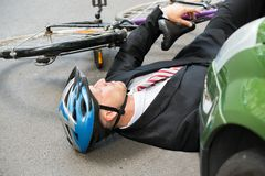 Male cyclist after road accident. Unconscious Male Cyclist Lying On Street After Road Accident Stock Images