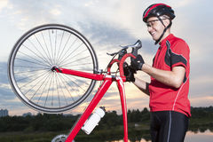 Male Cyclist Standing With Bicycle Outdoors Against Sunset. Sport Concepts. Portrait of Male Cyclist Standing With Bicycle Outdoors Against Sunset. Equipped in Stock Photography