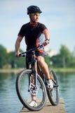 Male cyclist taking break next to bike near city lake royalty free stock photos