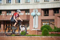 Male cyclist training on street edging. Male professional cyclist riding bike on street edging near flowerbeds and trees in front of red building. Sportsman Royalty Free Stock Images