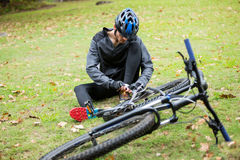 Male cyclist tying a shoelaces in park. Male cyclist tying a shoelaces outdoors in park Royalty Free Stock Images