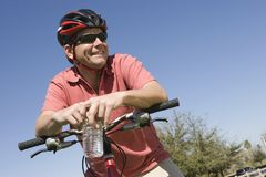 Male Cyclist With Water Bottle Against Sky. Happy male cyclist holding water bottle and bicycle against blue sky Stock Images