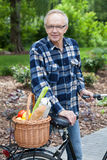Male cyclist with wicker basket full of groceries Stock Image