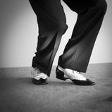 Male dancer dancing shoes. Male latin and salsa dancer in black and white jazz dancing shoes in light and dark on stage Royalty Free Stock Image