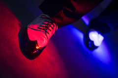 Male dancer dancing shoes. Male latin and salsa dancer in black and white jazz dancing shoes in light and dark on stage in nightclub dicoteque on dancefloor Stock Image