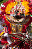 Male dancer dressed in orange and red feathers, dances in Junkanoo, a traditional island cultural parade. Royalty Free Stock Photos