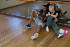 Male dancer with friend using digital tablet in studio Stock Photo