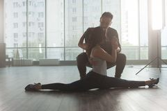Male dancer looking at his partner while she`s doing a slip in practice room. Graceful lady dancer stock photography