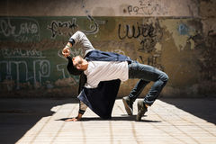 Male dancer practicing a dance routine. Young male hip hop dancer arching back and showing some of his dance moves in an urban setting with graffiti walls stock image