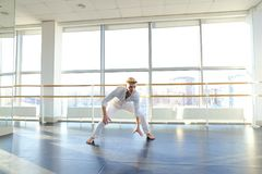 Guy spotting in white suit and raving at studio. Male dancer rejoicing victory at competition at gym. Young person looks fashion in white suit. Concept of Stock Photography