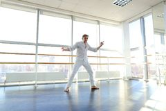 Guy spotting in white suit and raving at studio. Male dancer rejoicing victory at competition at gym. Young person looks fashion in white suit. Concept of Royalty Free Stock Photos