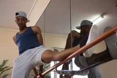 Male dancer stretching leg by mirror on barre. In dance studio Royalty Free Stock Image