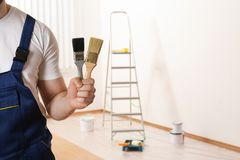 Male decorator with paint brushes in empty room. Space for text stock images