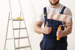 Male decorator with paint roller in empty room. Space for text stock photo