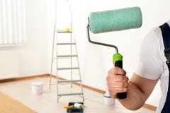 Male decorator with paint roller in empty room. Space for text royalty free stock photo