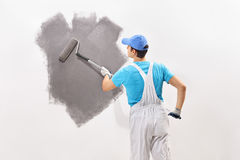 Male decorator painting a wall with gray color. Rear view shot of a young male decorator in white overalls painting a wall with gray color Stock Image