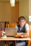 Male deltagare i pizzeria med bärbar dator Arkivbild