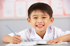 Male deltagare som fungerar på skrivbordet i kinesisk skola royaltyfri fotografi