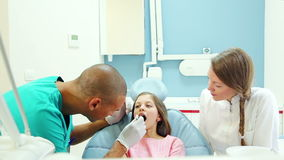 Male dental surgeon doing routine dental check up to lovely little girl stock video footage