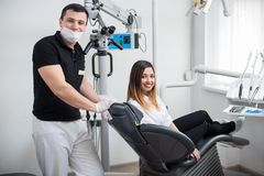 Male dentist with beautiful female patient after treatment in modern dental clinic. Woman sitting in the dental chair. Handsome male dentist with beautiful Stock Photography