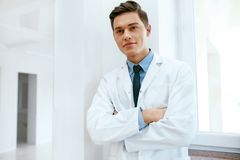 Male Dentist Doctor In Dental Clinic. Portrait. Of Happy Dentistry Doctor Wearing White Coat. High Resolution stock images