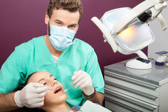 Male dentist examines mouth of woman on the dentist's chair Royalty Free Stock Image
